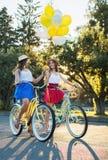 Dois amigos fêmeas novos à moda em uma bicicleta no parque Melhores amigos que apreciam um dia na bicicleta Foto de Stock Royalty Free