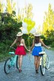 Dois amigos fêmeas novos à moda em uma bicicleta no parque Melhores amigos que apreciam um dia na bicicleta Fotos de Stock