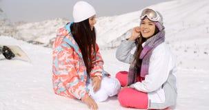 Dois amigos fêmeas novos que conversam na neve Imagens de Stock Royalty Free
