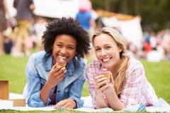 Dois amigos fêmeas que apreciam queques no evento exterior do verão fotos de stock
