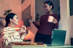Dois amigos fêmeas que comem a pizza e que bebem o chá imagem de stock