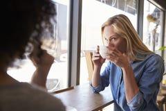 Dois amigos fêmeas que encontram-se na cafetaria foto de stock royalty free