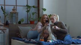 Dois amigos fêmeas que olham o índice dos meios no telefone video estoque