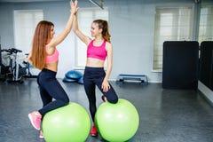 Dois amigos fêmeas que vestem o sportswear que dá a elevação cinco quando exercício no gym fotos de stock