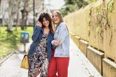 Dois amigos felizes das jovens mulheres que abraçam na rua fotografia de stock royalty free