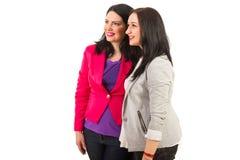 Dois amigos felizes das mulheres que olham afastado Foto de Stock