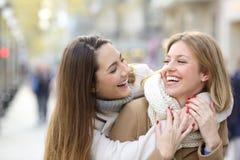 Dois amigos felizes que gracejam na rua no inverno imagem de stock royalty free