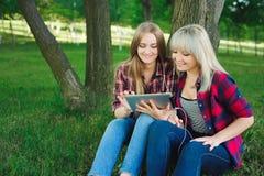 Dois amigos felizes que procuram o índice dos meios em linha em um portátil que senta-se na grama em um parque fotografia de stock royalty free