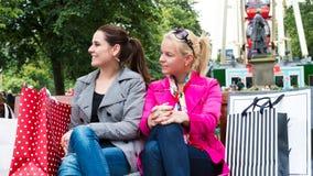 Dois amigos fêmeas novos atrativos que apreciam um dia para fora após a compra bem sucedida Imagens de Stock