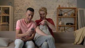 Dois amigos homossexuais internacionais sentam-se no sofá e olham-se imagens engraçadas no smartphone Cosiness home, família video estoque