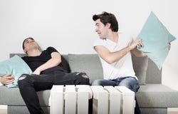Dois amigos masculinos adormecidos no cinza agradável do treinador em casa O homem na camisa branca que acorda seu amigo com um d Fotografia de Stock