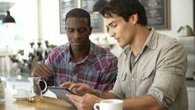Dois amigos masculinos na cafetaria que olha a tabuleta de Digitas filme