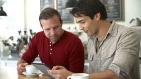Dois amigos masculinos na cafetaria que olha a tabuleta de Digitas video estoque