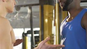 Dois amigos masculinos que têm o argumento no gym, diferença nas opiniões, desacordo video estoque