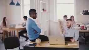 Dois amigos multi-étnicos novos falam, cooperam no escritório saudável moderno Os colegas discutem o trabalho, discutem no local  video estoque
