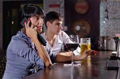 Dois amigos na barra com uma mulher em um móbil Fotos de Stock Royalty Free