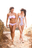 Dois amigos nos biquinis que andam entre rochas no th Fotografia de Stock