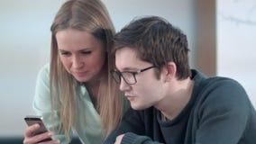 Dois amigos novos que sentam-se na tabela na escola e que trabalham no smartphone Foto de Stock