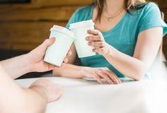 Dois amigos ou pares que mantêm os copos de café unidos imagem de stock