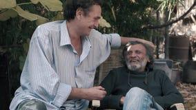 Dois amigos, pai e filho rindo ao sentar-se fora vídeos de arquivo