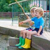 Dois amigos pequenos adoráveis que pescam com haste selfmade Foto de Stock