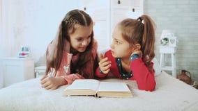 Dois amigos pequenos, estão nos pijamas e neles livro de leitura Falam e discutem o livro vídeos de arquivo
