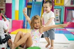 Dois amigos pequenos que jogam junto no campo de jogos Imagens de Stock Royalty Free