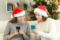 Dois amigos que compartilham do índice do telefone no Natal imagem de stock royalty free