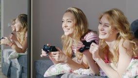 Dois amigos que jogam na consola de computador Encontrar-se na cama, guardando cola em suas mãos Emocionalmente reaja, ria filme
