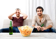 Dois amigos que olham a televisão em casa imagens de stock royalty free