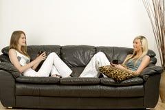 Dois amigos que relaxam no sofá Fotografia de Stock Royalty Free