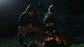 Dois amigos que sentam-se na noite ao lado do fogo e da fala da fogueira video estoque