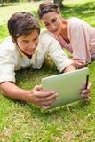 Dois amigos que sorriem como olham algo em uma tabuleta junto Fotos de Stock Royalty Free