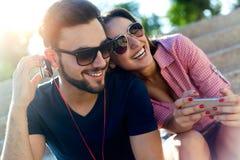 Dois amigos que usam o telefone celular e escutando a música no estreptococo Fotos de Stock Royalty Free