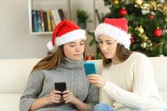 Dois amigos que usam telefones em feriados do Natal foto de stock