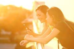 Dois amigos que usam um telefone esperto no por do sol imagem de stock