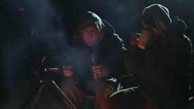 Dois amigos sentam-se ao lado da fogueira na madeira na noite, falando e bebendo o chá vídeos de arquivo