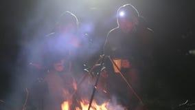 Dois amigos sentam-se ao lado da fogueira na madeira na noite, falando e bebendo o chá video estoque
