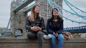 Dois amigos sentam-se em uma parede na ponte Londres da torre filme