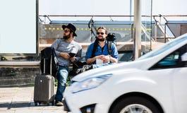 Dois amigos, turistas estão esperando o ônibus que não chega Imagem de Stock Royalty Free