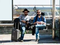 Dois amigos, turistas estão esperando o ônibus que não chega Fotografia de Stock Royalty Free