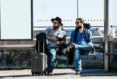 Dois amigos, turistas estão esperando o ônibus que não chega Foto de Stock Royalty Free