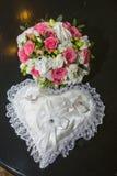 Dois anéis casamento, descanso na forma de um coração, um ramalhete de rosas vermelhas e brancas Fotografia de Stock Royalty Free