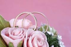 Dois anéis de casamento dourado em flores Imagem de Stock Royalty Free