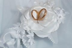 Dois anéis de ouro e fundos do casamento Imagens de Stock Royalty Free
