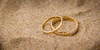 Dois anéis de ouro na areia fotografia de stock royalty free
