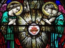 Dois anjos com o coração sagrado no vitral Fotos de Stock Royalty Free