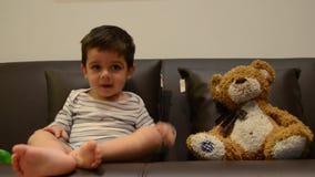 Dois anos bonitos do menino idoso que olha a tev? com seu urso de peluche vídeos de arquivo