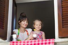 Dois anos de menina idosa com a mãe que senta-se no peitoril da janela com os obturadores marrons de madeira europeus tradicionai Imagens de Stock Royalty Free