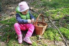 Dois anos de menina idosa com uma cesta completa dos cogumelos Imagem de Stock Royalty Free